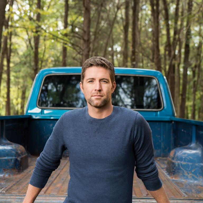 JOSH TURNER SURPRISES NEWCOMER DREW BALDRIDGE ON STAGE AT THE GRAND OLE OPRY.